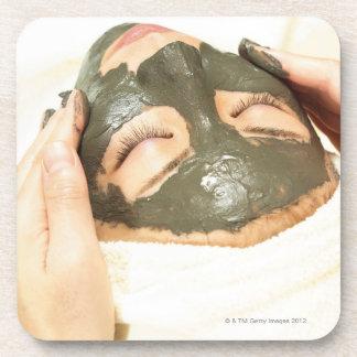 Estético que frota el paquete de fango en la cara posavaso