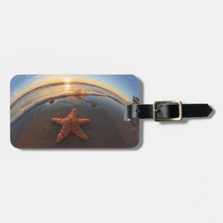 Estrellas de mar en la playa en la puesta del sol etiqueta de maleta