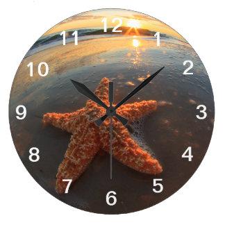 Estrellas de mar y burbujas en la puesta del sol reloj redondo grande