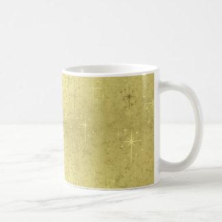 Estrellas de oro del navidad en el papel de la taza clásica