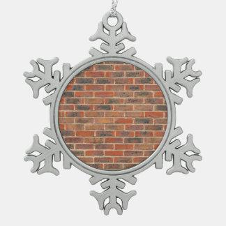Estructura roja de la pared de ladrillo adorno de peltre en forma de copo de nieve