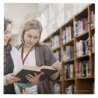 Estudiante de ayuda del bibliotecario con la inves azulejo cuadrado grande