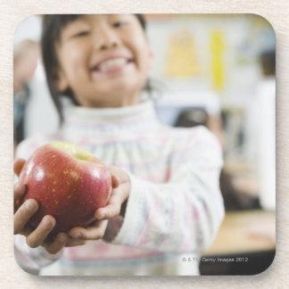 Estudiante elemental que sostiene una manzana en posavasos de bebidas