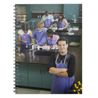 Estudiante hispánico que se coloca en laboratorio libros de apuntes con espiral