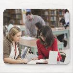 Estudiante que habla con el bibliotecario en tapetes de ratones