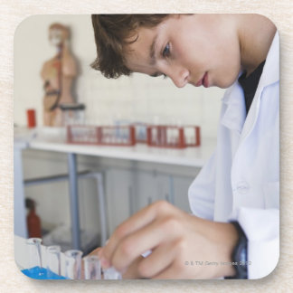 Estudiante que hace el experimento de la ciencia posavasos de bebida