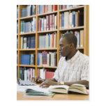 Estudiante universitario que trabaja en biblioteca tarjetas postales