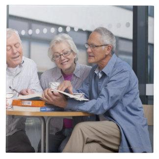 Estudiantes adultos que estudian junto en café azulejo cuadrado grande