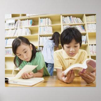 Estudiantes de la escuela primaria que leen un lib poster