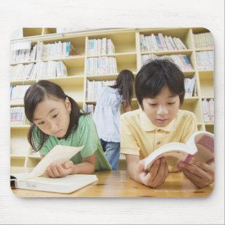 Estudiantes de la escuela primaria que leen un mouse pad