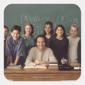 Estudiantes de la escuela primaria que se colocan pegatina cuadrada
