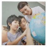 Estudiantes elementales y profesor que miran teja cerámica