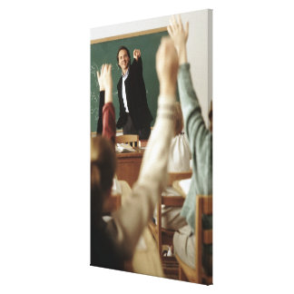 Estudiantes que aumentan sus manos en sala de clas lienzo envuelto para galerías