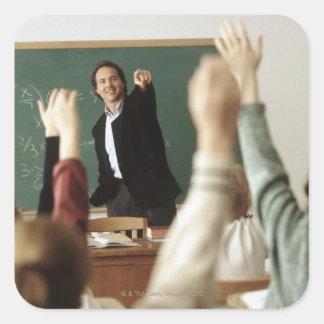 Estudiantes que aumentan sus manos en sala de pegatina cuadrada