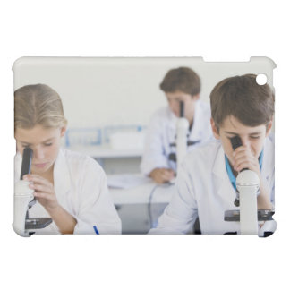Estudiantes que miran a través de los microscopios