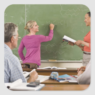 Estudiantes y profesor en sala de clase pegatina cuadrada