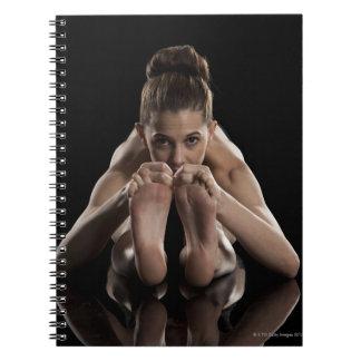 Estudio tirado de yoga practicante de la mujer.  cuadernos