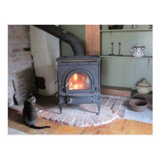 Estufa de madera del país con el gato postales