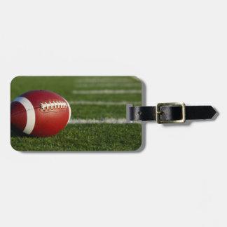 Etiqueta del equipaje del fútbol con la correa de etiqueta para maleta