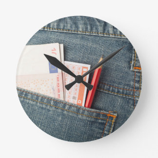 Euro money and lottery bet slip in pocket round clock