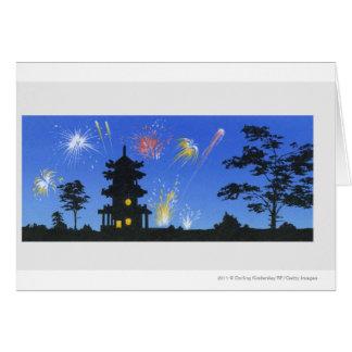 Exhibición del fuego artificial y silueta de la tarjeta de felicitación