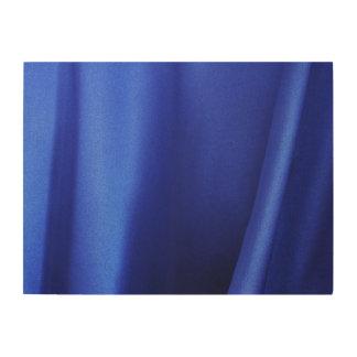 Extracto azul de la tela de seda que fluye impresiones en madera