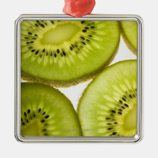 Extreme close-up of four pieces of sliced kiwi metal ornament