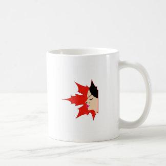 Face of a pretty lady in a maple leaf coffee mug