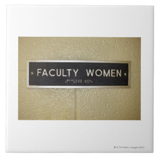 Faculty women sign large square tile