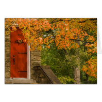 Fall Leaves and Historical Church With Red Door