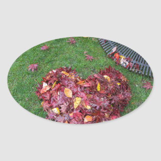 Fall Leaves Raked into Heart Shape on Green Grass Oval Sticker
