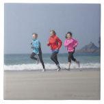 Familia que corre junto en la playa azulejos