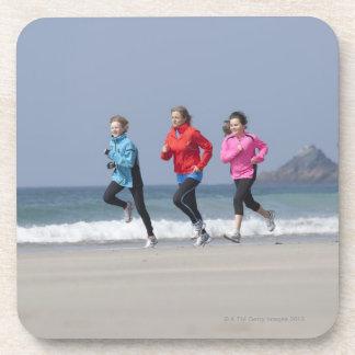 Familia que corre junto en la playa posavasos
