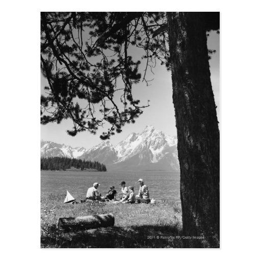 Family having picnic by lake mountains postcard