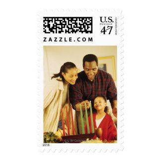Family lighting the Kinara for Kwanzaa Postage