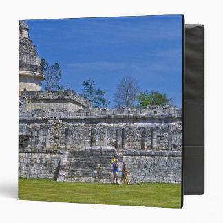 Family of tourists walk past ancient Mayan Binder