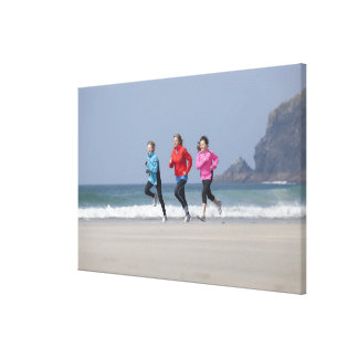 Family running together on beach canvas print