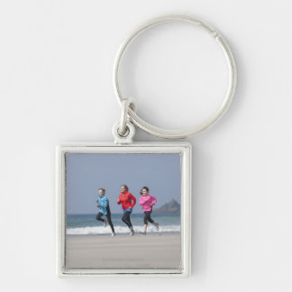Family running together on beach keychain