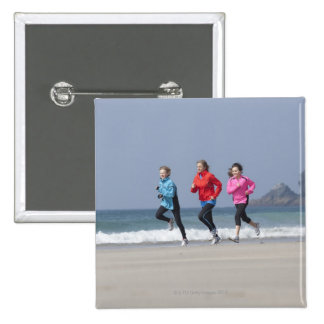 Family running together on beach pinback button