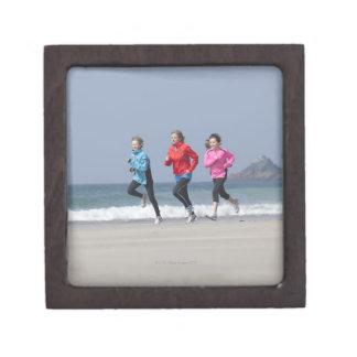 Family running together on beach premium gift box
