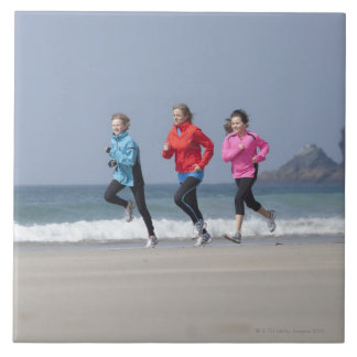 Family running together on beach tile