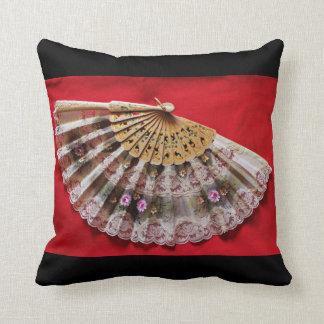 Fan de mano adornada en un fondo rojo cojín decorativo
