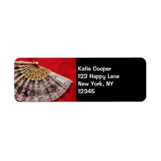 Fan de mano adornada en un fondo rojo etiquetas de remite