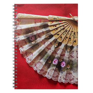 Fan de mano adornada en un fondo rojo libro de apuntes