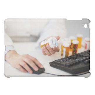 Farmacéutico con las botellas de píldora en el ord