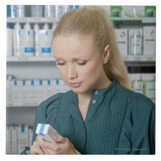 Farmacéutico de sexo femenino que mira la medicina azulejo cuadrado grande