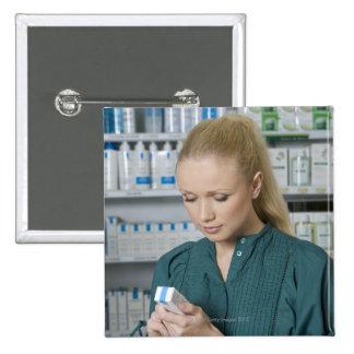Farmacéutico de sexo femenino que mira la medicina pins