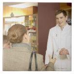 Farmacéutico de sexo masculino que entrega la medi azulejo cuadrado grande