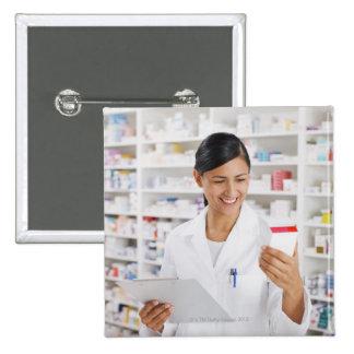 Farmacéutico en la farmacia que sostiene el tabler pin