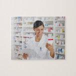 Farmacéutico en la farmacia que sostiene el tabler rompecabezas con fotos